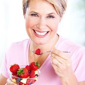 Middle-aged woman eating a bowl of fruit and smiling
