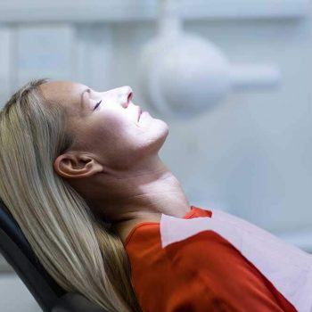 middle-aged female patient relaxing in the dental chair