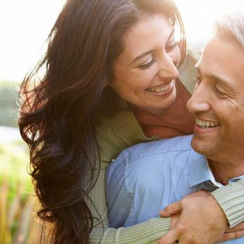 Middle-aged couple smiling with their arms wrapped around each other outdoors